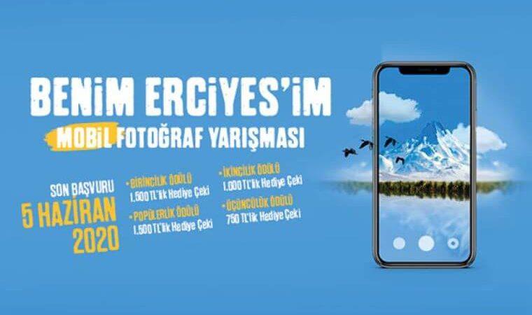 Kapadokya Üniversitesi Benim Erciyes'im Mobil Fotoğraf Yarışması duyuru görselidir. Görselde mavi fonda bir cep telefonuyla Erciyes Dağı'nın fotoğrafının çekildiği görülmektedir. Ayrıca yarışma bilgileri yer almaktadır.