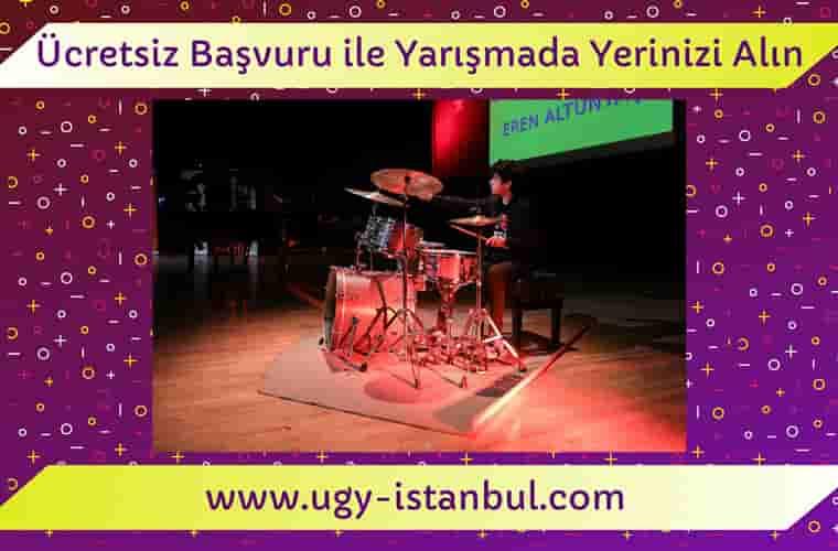 Görselde mor fon üzerinde sahnede bateri çalan bir çocuğun fotoğrafı yer almaktadır. Ücretsiz başvuru ile Yarışmada yerinizi alın yazısı ve ugy-istanbul.com web sitesi adresi yazılmıştır.