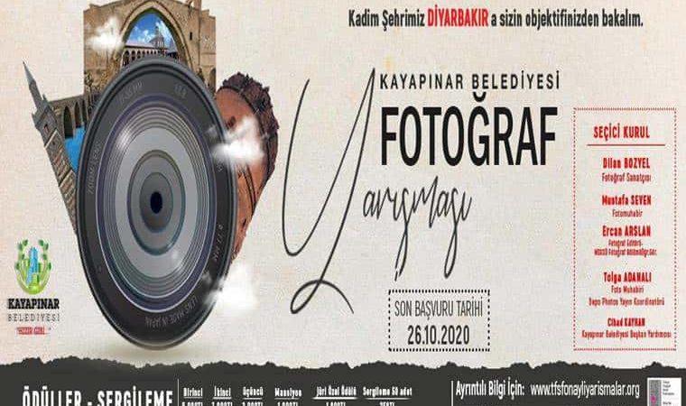 Kayapınar Belediyesi Ulusal Fotoğraf Yarışması duyuru görselidir. Görselde fotoğraf makinası vizörünün etrafında Diyarbakır iline ait tarihi ve doğal güzelliklere ait görüntüler görünmekte.