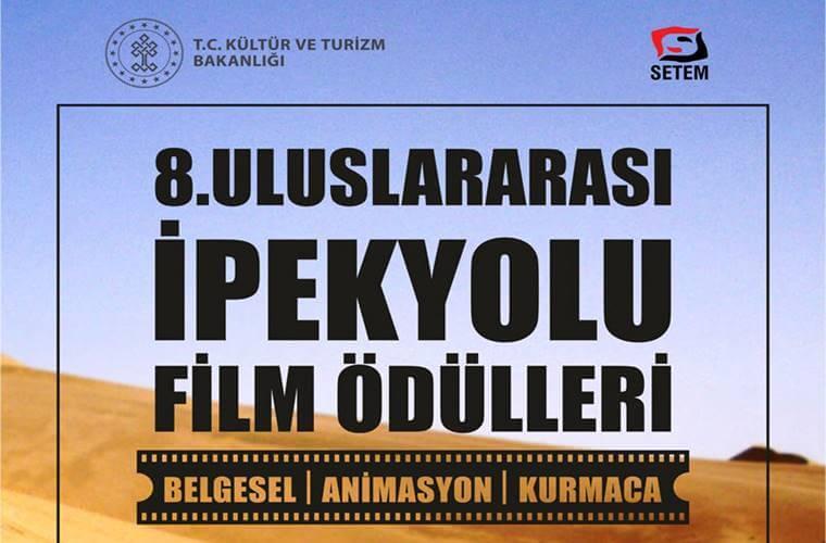 Uluslararası İpek Yolu Film Ödülleri duyuru görselidir. Görselde sarı çöl ve mavi gökyüzü görülmekte ve program adı yazmaktadır.